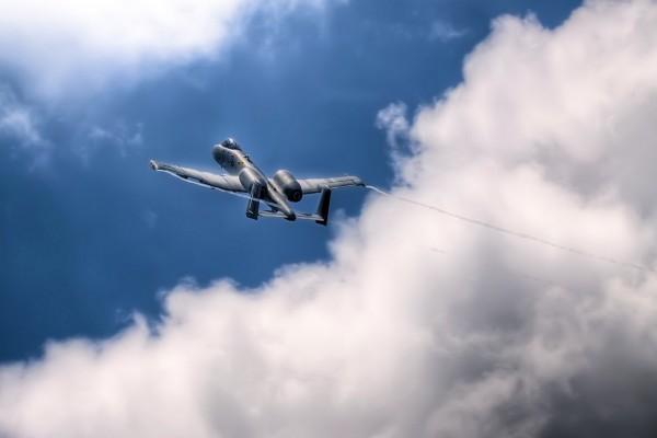 Avión militar volando junto a las nubes