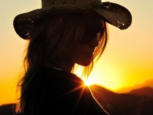 Mujer con un sombrero y gafas de sol al atardecer