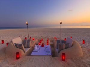 Romántica cena con velas en la arena de una playa