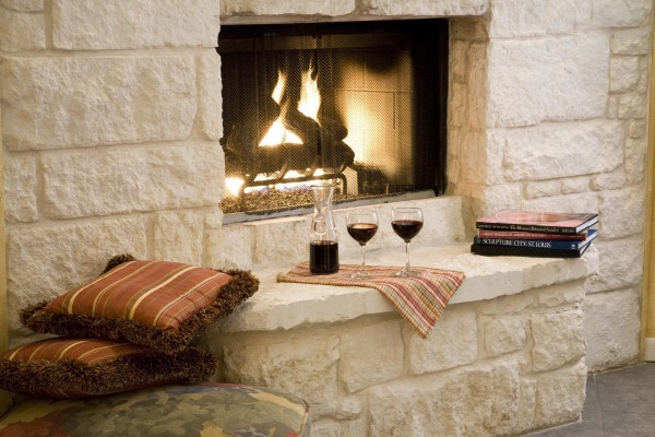 Dos copas de vino junto a una ardiente chimenea