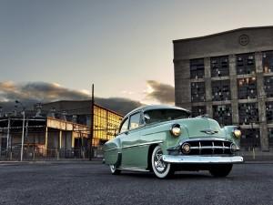 Un Chevrolet antiguo junto a una fábrica