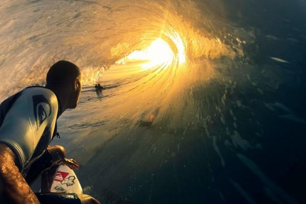 Surfista tomando una ola iluminada por el sol