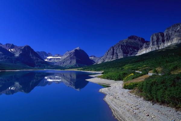 Lago y montañas bajo un deslumbrante cielo azul
