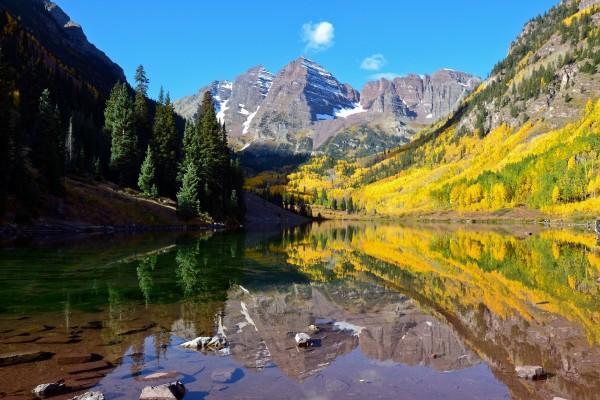 Árboles otoñales en las montañas reflejados en el lago
