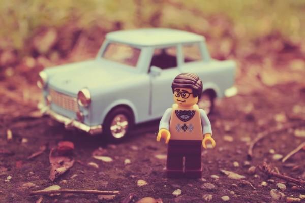 Hombre Lego junto a un coche azul