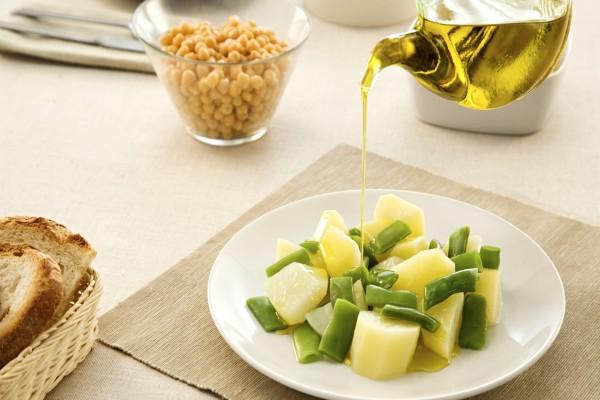 Aliñando con aceite de oliva unas ricas patatas con judías verdes