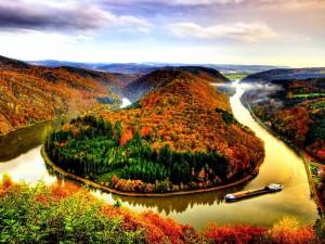 Barco navegando por un río en otoño