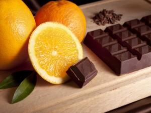 Jugosas naranjas y mandarina junto a una barra de chocolate