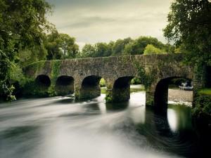 Río fluyendo bajo un puente de piedra
