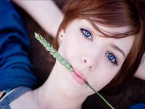 Chica con una espiga verde en la boca