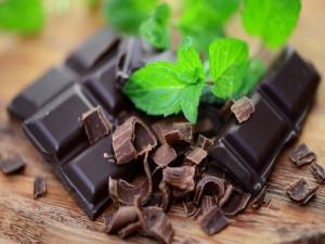 Hojas de menta sobre unas onzas de chocolate negro