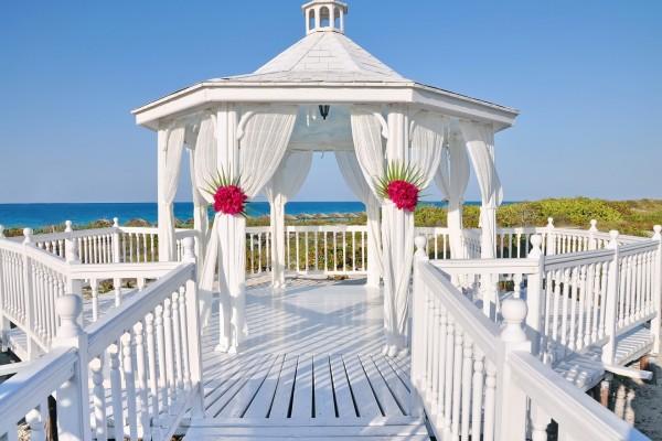 Gazebo blanco con cortinas junto a una playa