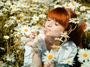 Mujer disfrutando del aroma de las margaritas