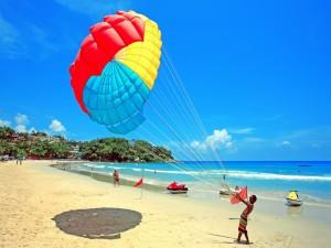 Chico sosteniendo las correas de un paracaídas acuático