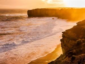 Los rayos de sol iluminan los acantilados y la playa