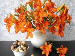 Postal: Lirios naranjas en un florero junto a un platillo con bombones