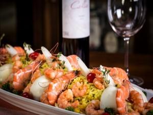 Ensalada de arroz con camarones junto a una botella de vino