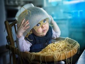 Bebé travieso volcando una fuente de espaguetis