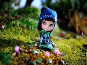 Muñeca sentada en el suelo cubierto de musgo