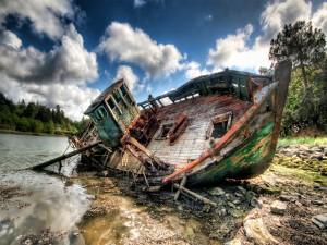 Viejo barco tumbado en la orilla de un río