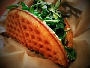 Un gofre sándwich con rúcula y queso