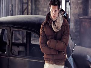 Un chico guapo apoyado en un coche antiguo