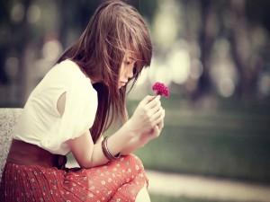 Chica contemplando una flor