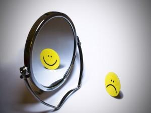 Emoticono reflejado en un espejo