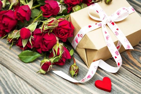 Ramo de rosas rojas y un regalo atado con una cinta