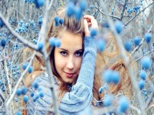 Chica hermosa entre unos matorrales con frutas de color azul