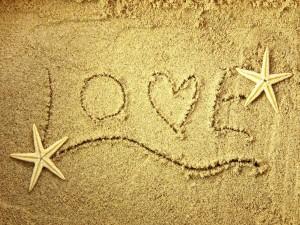 Love escrito en la arena junto a dos estrellas de mar