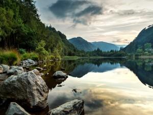 Nubes y montañas reflejadas en el lago