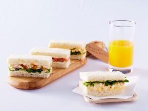 Zumo de naranja junto a unos ricos sándwich variados