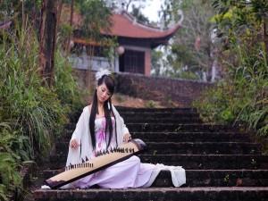 Mujer sentada en las escaleras con un instrumento musical