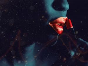 Mujer pintándose los labios con un color escarlata