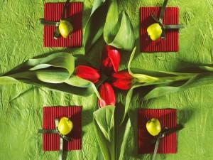 Cuatro tulipanes rojos sobre un mantel verde