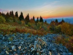 El ocaso del sol en un paisaje con montañas, árboles y piedras