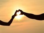 Pareja formando un corazón a la luz del sol