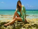 Modelo sentada en unas rocas junto al mar