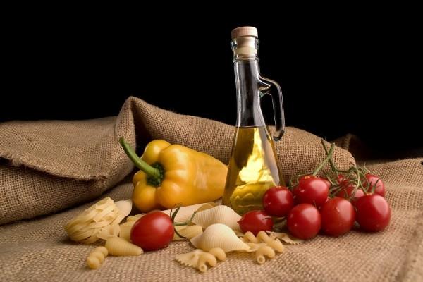 Varios tipos de pasta seca junto a unos tomates