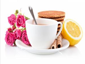 Rosas y galletas junto a una taza de té
