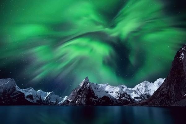 Aurora boreal sobre un lago y montañas cubiertas de nieve