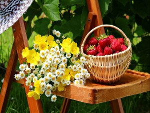 Cesta con fresas junto a un ramo de flores silvestres