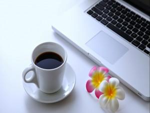 Taza de café junto a un ordenador