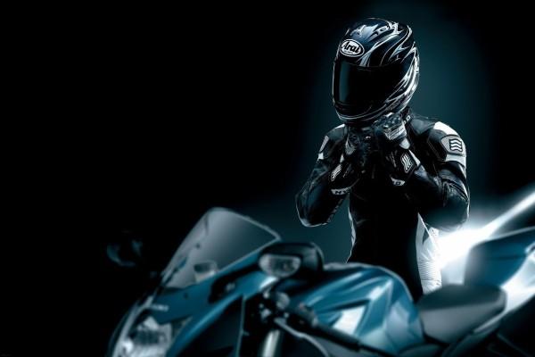 Hombre junto a su moto ajustándose el casco