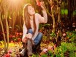 Chica sentada entre flores