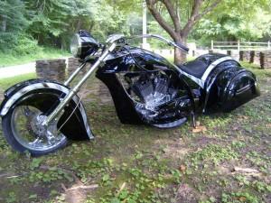 Una gran moto negra en un jardín