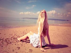 Chica sentada en una playa observando el mar