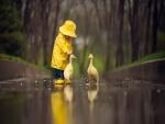 Bebé con impermeable amarillo junto a unos patitos