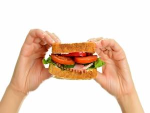 Manos sosteniendo un sándwich